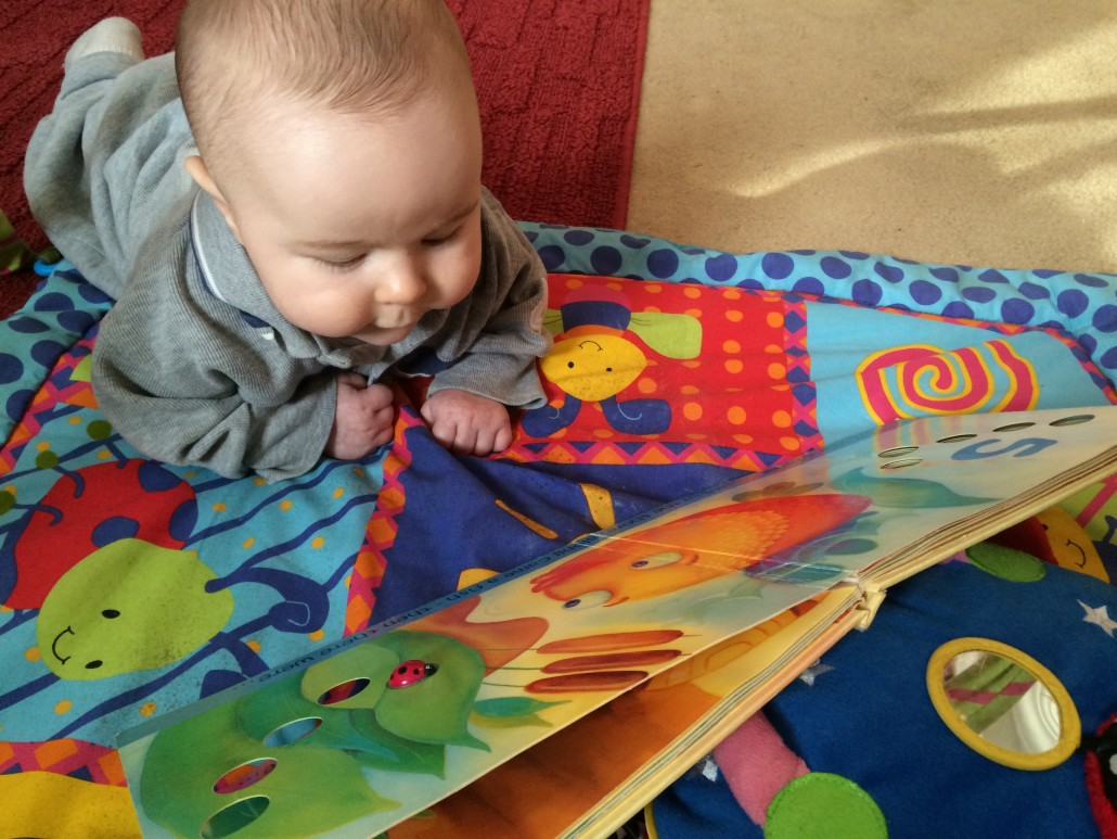 3 month old baby looks at a book while doing tummy time