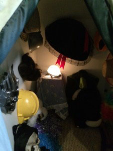 hats hanging on a wall in the corner of a closet for dress up