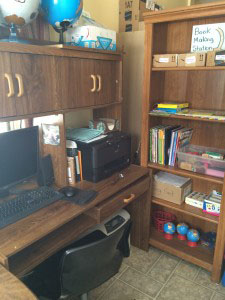 computer table and shelves organized with learning supplies for kids