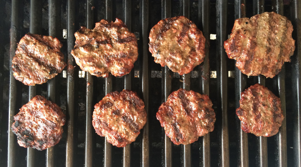 eight grilled hamburgers with grill marks on a grill