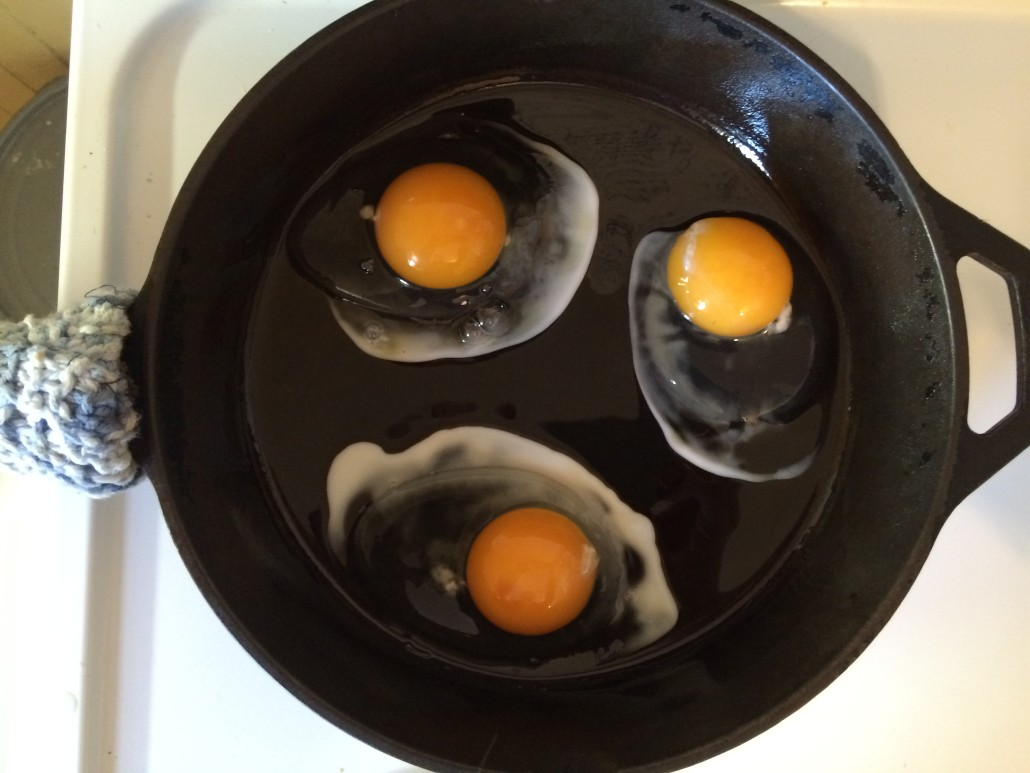 three sunny side up eggs just starting to cook in a cast iron skillet