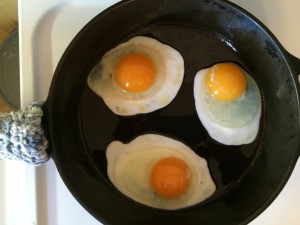three sunny side up eggs cooked halfway through on a cast iron skillet