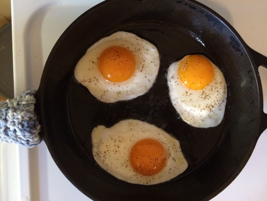 three sunny side up eggs almost ready to flip on a cast iron skillet