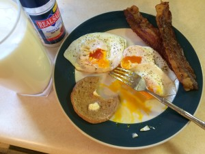 three sunny side up eggs, sourdough muffin, bacon, and milk make the perfect breakfast