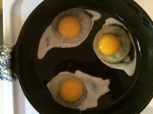 fried eggs just starting to cook in a cast iron skillet