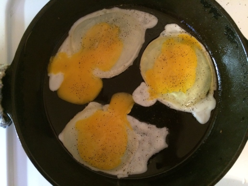 fried eggs halfway cooked with yolks broken
