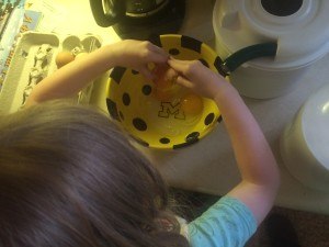 child cracking eggs into a bowl