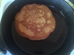sort of sourdough pancake cooking in a cast iron skillet