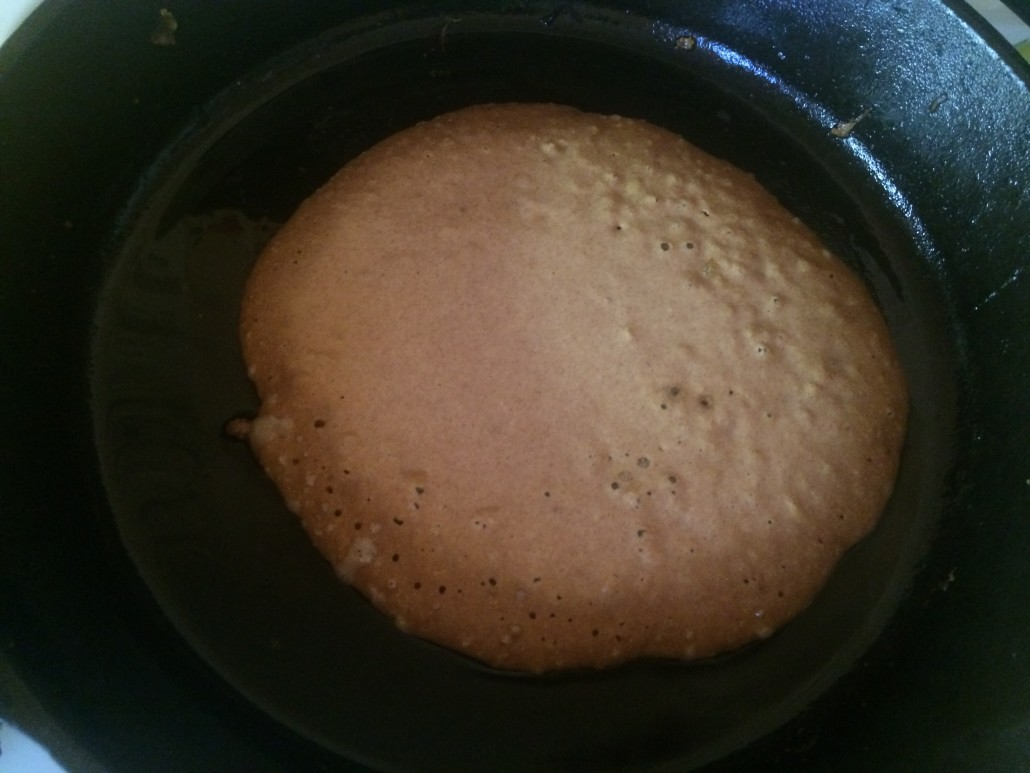 Sort of sourdough pancake with brown edges and bubbling on top ready to flip