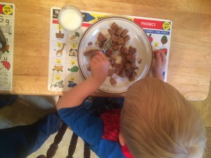 child eating whole wheat pancakes for breakfast with a glass of milk