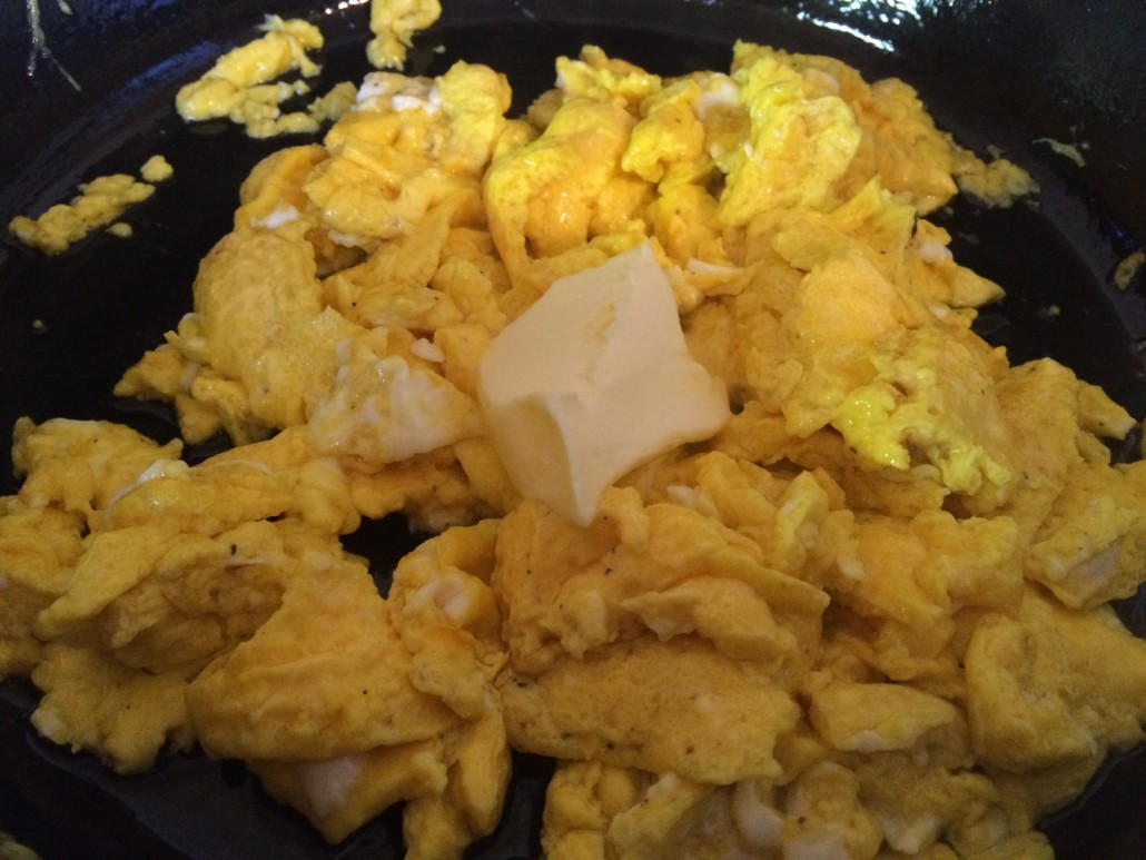 cooked scrambled eggs with melting butter in a cast iron skillet