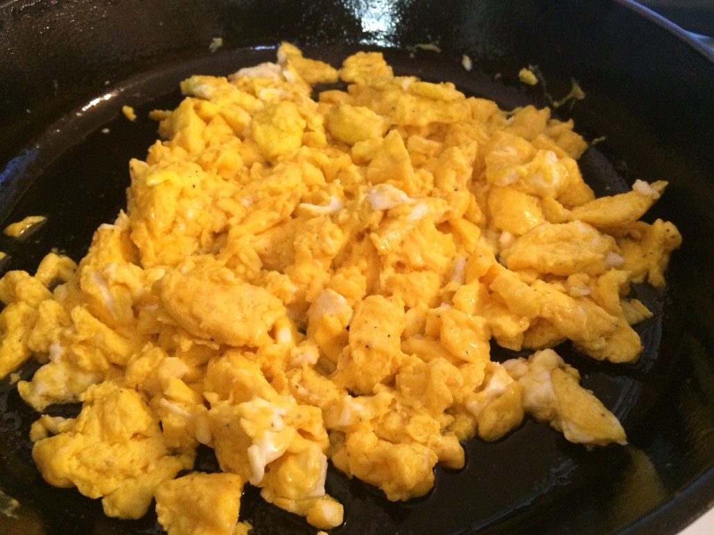 cooked scrambled eggs with butter and salt in a cast iron skillet