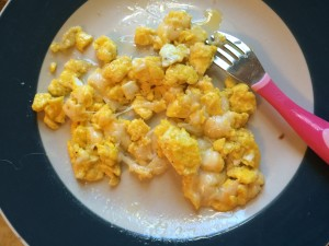 cooked scrambled eggs with melted cheese on a plate with a kids fork
