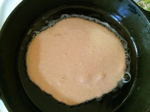 whole wheat pancake batter just starting to cook on a cast iron skillet