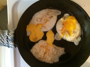 fried eggs ready to flip in a cast iron skillet