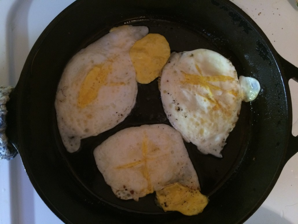 fried eggs cooked and flipped in a cast iron skillet
