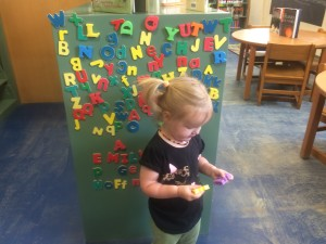 Ophelia Playing with Magnet Letters at Our Library