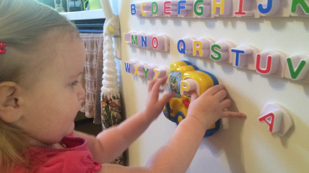 Ophelia Playing with Fridge Letter Magnets