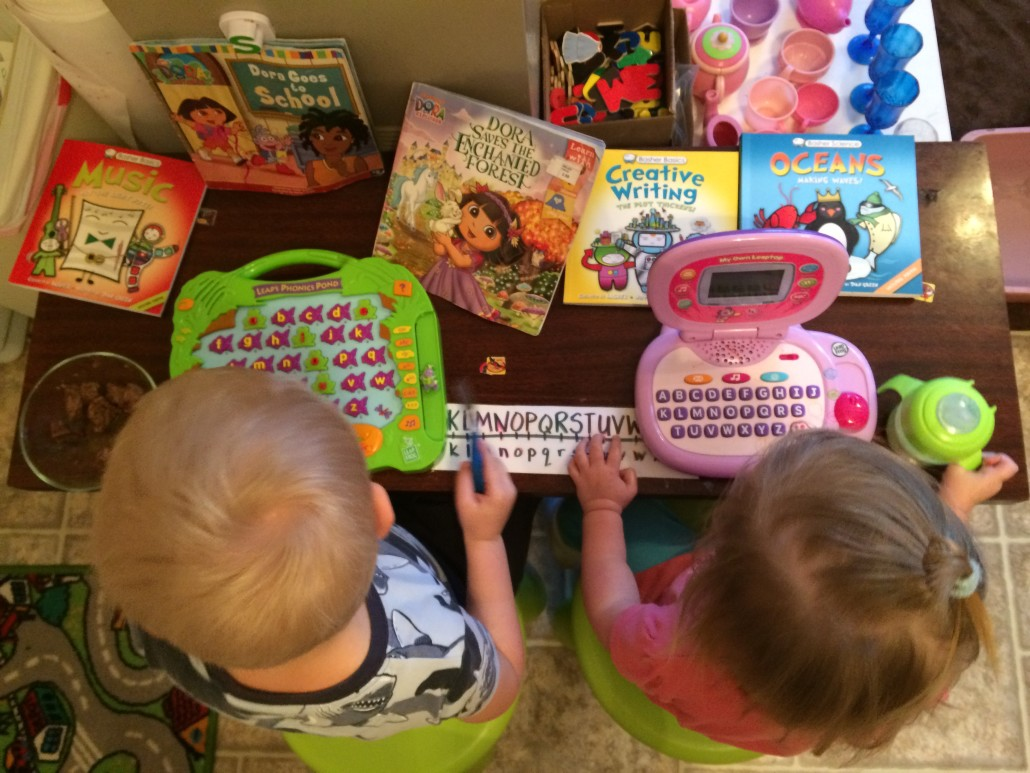 kids using ABC learning tablets at a coffee table sitting on little stools