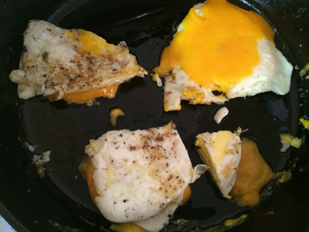 fried eggs with melted cheese folded and cut for an egg sandwich