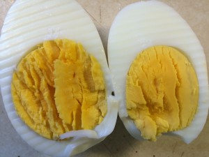 perfectly cooked hard boiled egg cut in half to show the yolks still soft