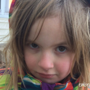 my five year old daughter outside wearing a winter coat and a serious look on her face