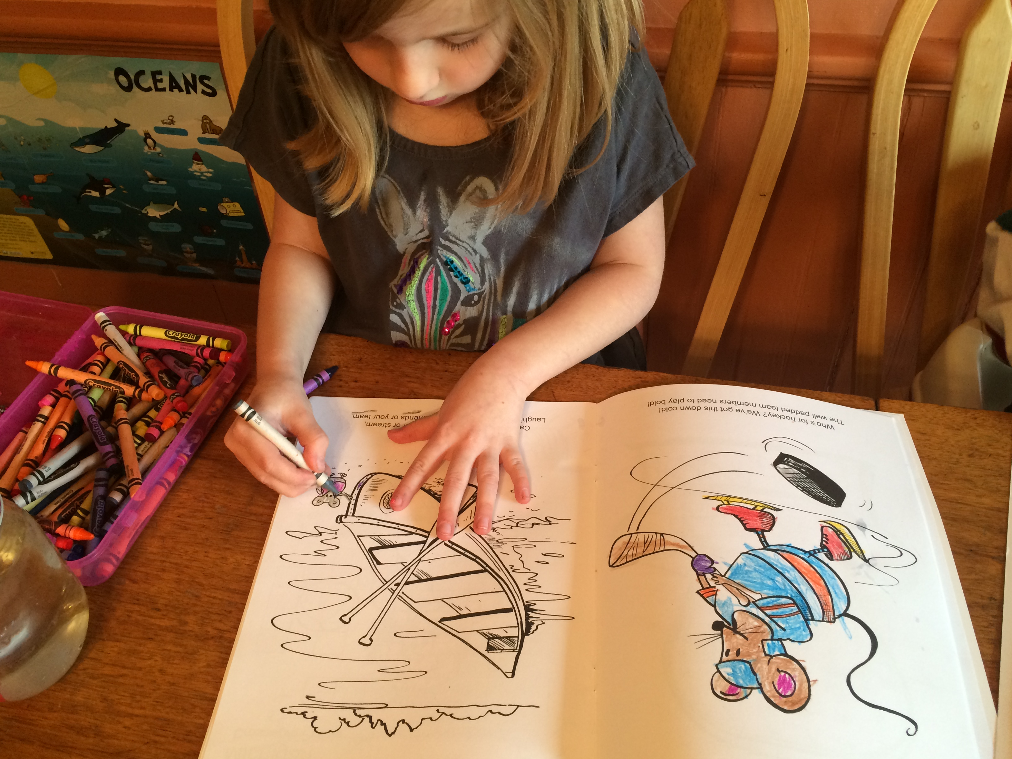 child carefully coloring a Michigan coloring book