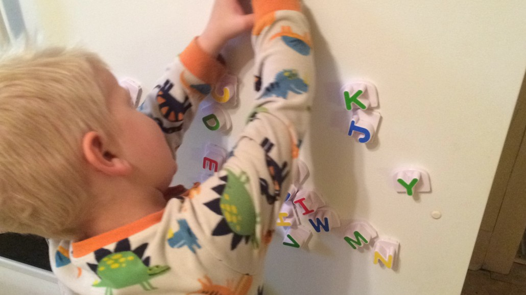 Elliot Smushes the Magnet Letters Around in Imaginative Play