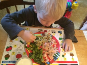 young child eating a salmon dinner with rice and broccoli