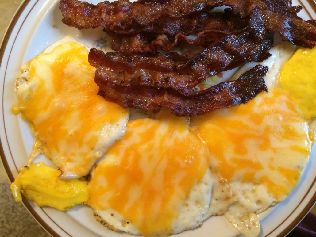 cooked fried eggs with melted cheese and bacon on a plate