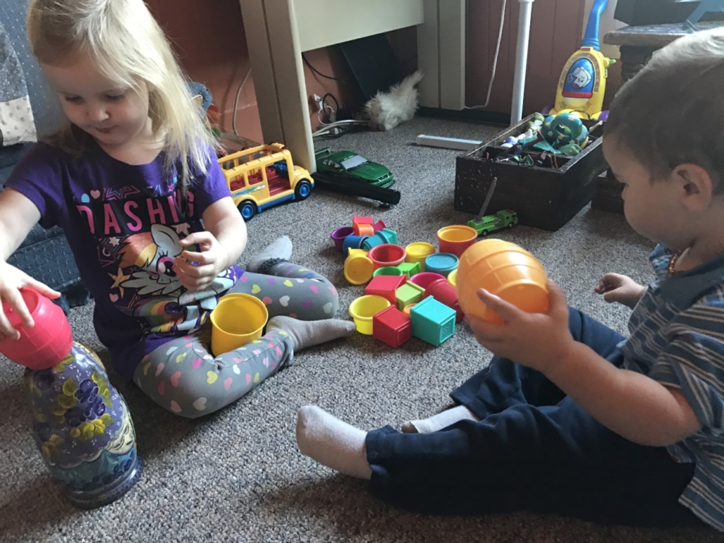 Ophelia and Julian Playing with Stacking Cups